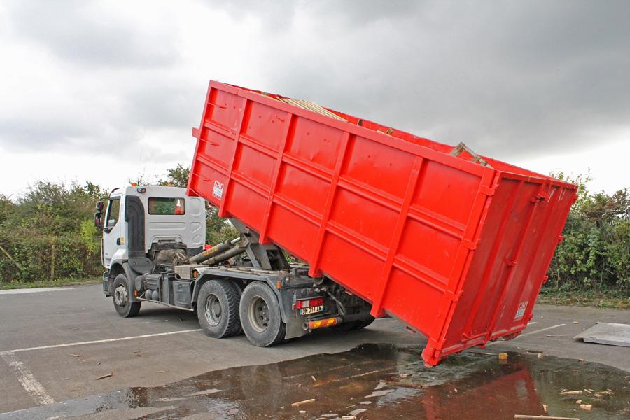 La benne à déchets glisse sur les rails du camion